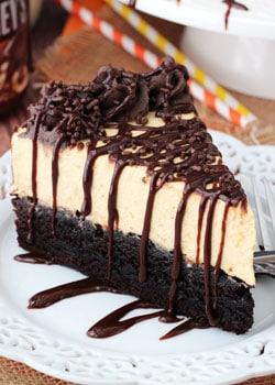 Pumpkin Chocolate Brownie Cheesecake slice on white plate