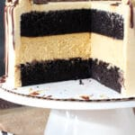 Chocolate Pumpkin Cheesecake Cake on white stand with slice missing