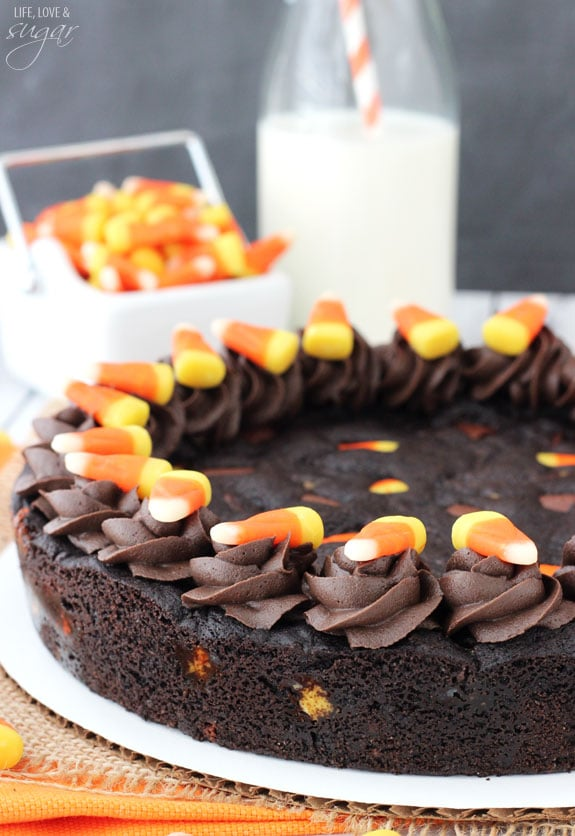 A Candy Corn Chocolate Chip Cookie Cake on a round piece of cardboard