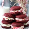 Red Velvet Cookie Sandwiches on white plate stacked with pink, red, white sprinkles
