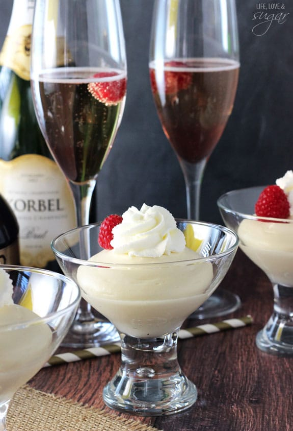 Champagne Mousse with whipped cream and raspberries in glass cups