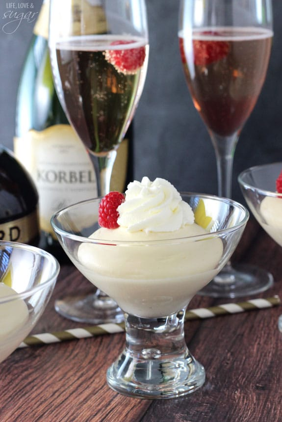 Mousse in a glass bowl with whipped cream and a raspberry on top with Black Raspberry Champagne Bellinis behind it