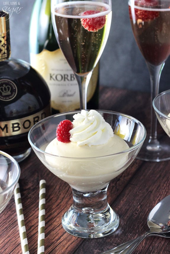 White mousse in a glass with whipped cream and a raspberry on top