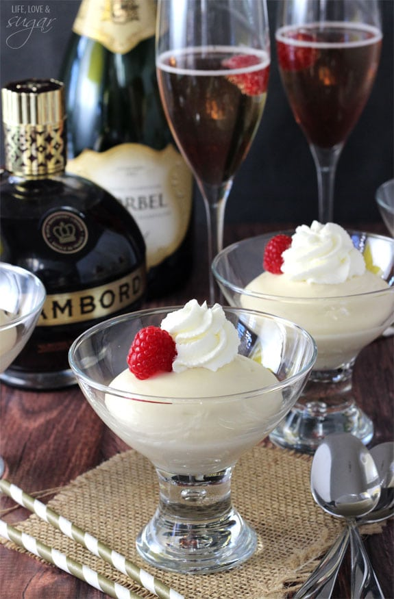 Two glasses with Mousse, whipped cream and a raspberries on top with Champagne Bellinis behind them