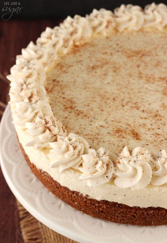 Homemade eggnog cheesecake decorated with swirls of whipped cream.