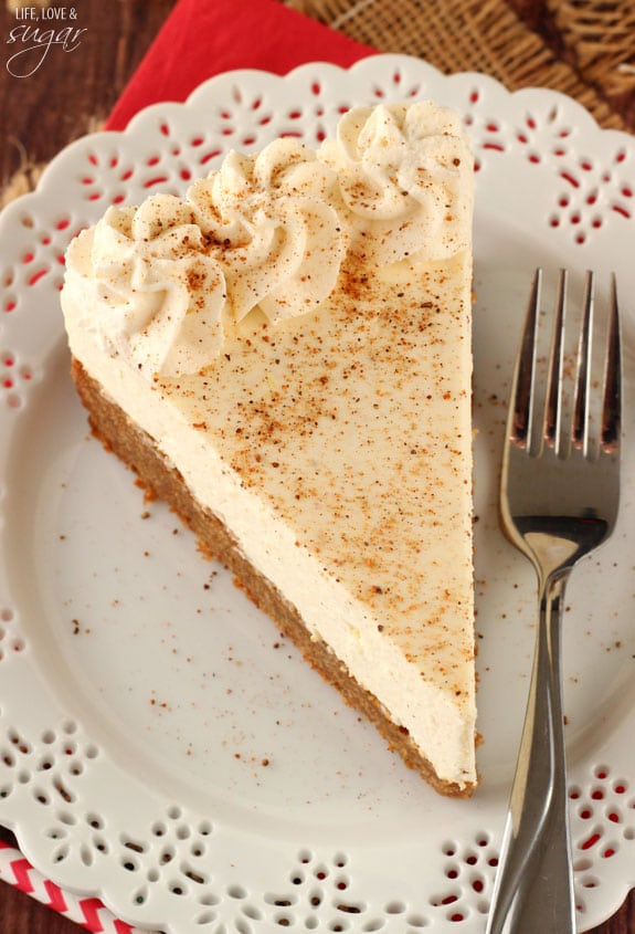 Sliced of eggnog cheesecake topped with swirls of whipped cream.