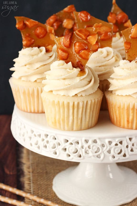 A bunch of BAILEYS® Macadamia Brittle Cupcakes on top of a white cake stand