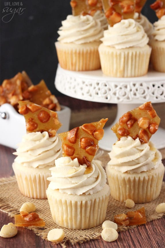 A bunch of cupcakes with icing and macadamia brittle on top surrounded by a cake stand and more nuts