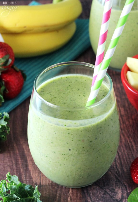 A green smoothie with two colorful straws in a short glass cup