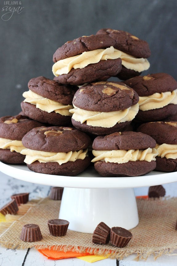 Peanut Butter Cookie Sandwiches stacked on white stand with Reese's cups around it