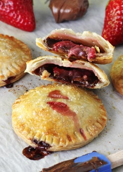 Strawberry Nutella Hand Pies on wax paper, one pie halved