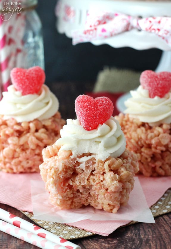 A Rice Krispie Treat Cupcake with a bite missing on pink napkin