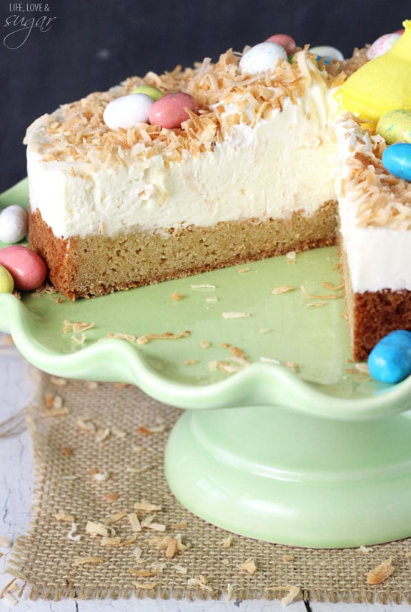 Coconut Blondie Cheesecake on a green cake stand with a slice removed