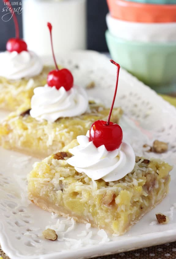 Pineapple Coconut Bars topped with whipped cream and a cherry on a platter