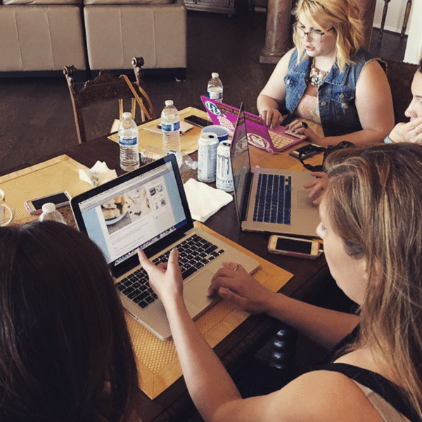 Three Women at a Dining Table Working on Their Laptops