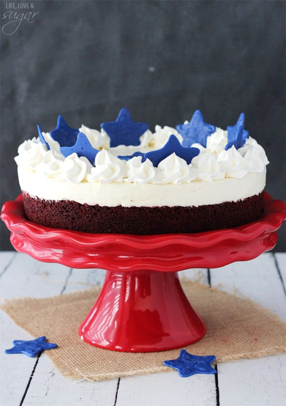 Red Velvet Blondie Cheesecake on a red cake stand topped with blue stars