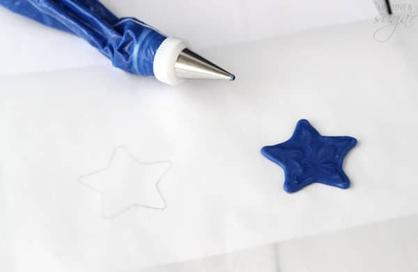 Blue frosting in a piping bag and a blue frosting star on parchment