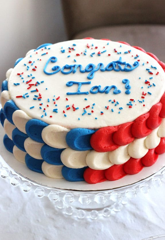 Red, white, and blue cake with Congrats Ian text on top