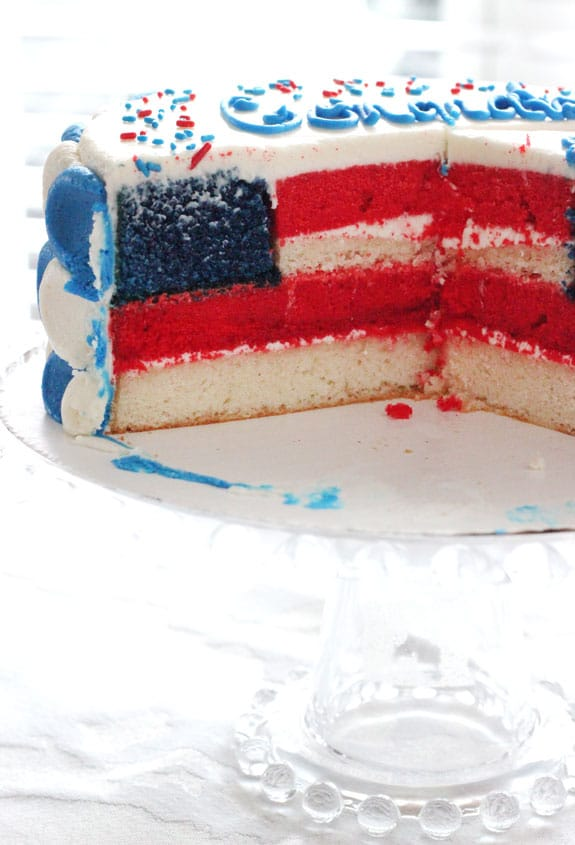 Side view of American flag cake with a couple slices removed