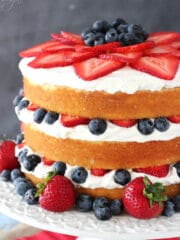 Fresh Berry Vanilla Layered Cake on white stand close up