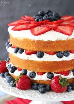 A Fresh Berry Vanilla Layered Cake on a White Cake Stand
