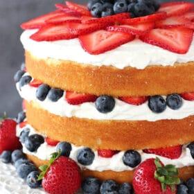 Fresh Berry Vanilla Layered Cake on white stand close up