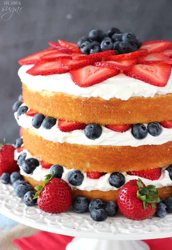 A Fresh Berry Vanilla Layered Cake on a White Cake Stand