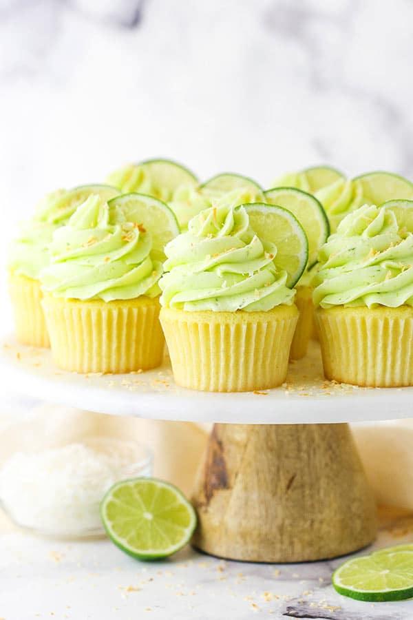 cupcakes de coco com limão em um suporte de mármore / madeira com fatias de limão na parte inferior