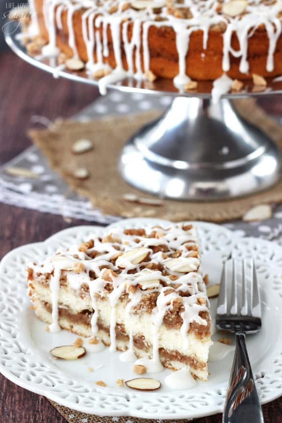 slice of Toffee Almond Streusel Coffee Cake on white plate with cake stand in background