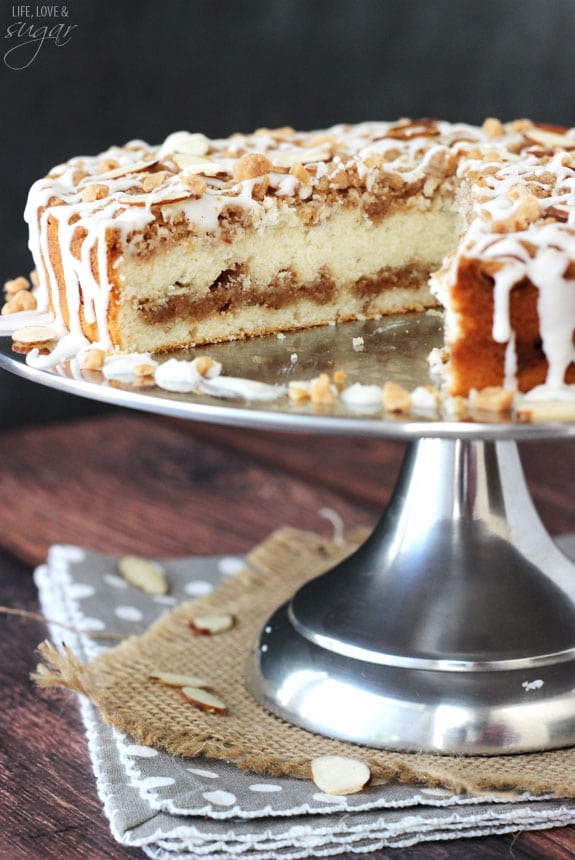 Toffee Almond Streusel Coffee Cake on silver cake stand with slice cut out