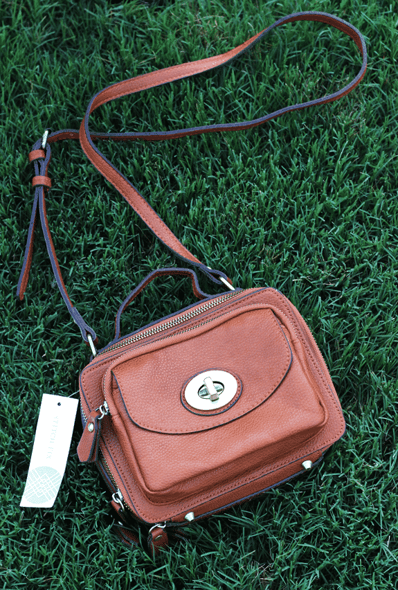 A Brown Purse with an Adjustable Shoulder Strap on the Grass