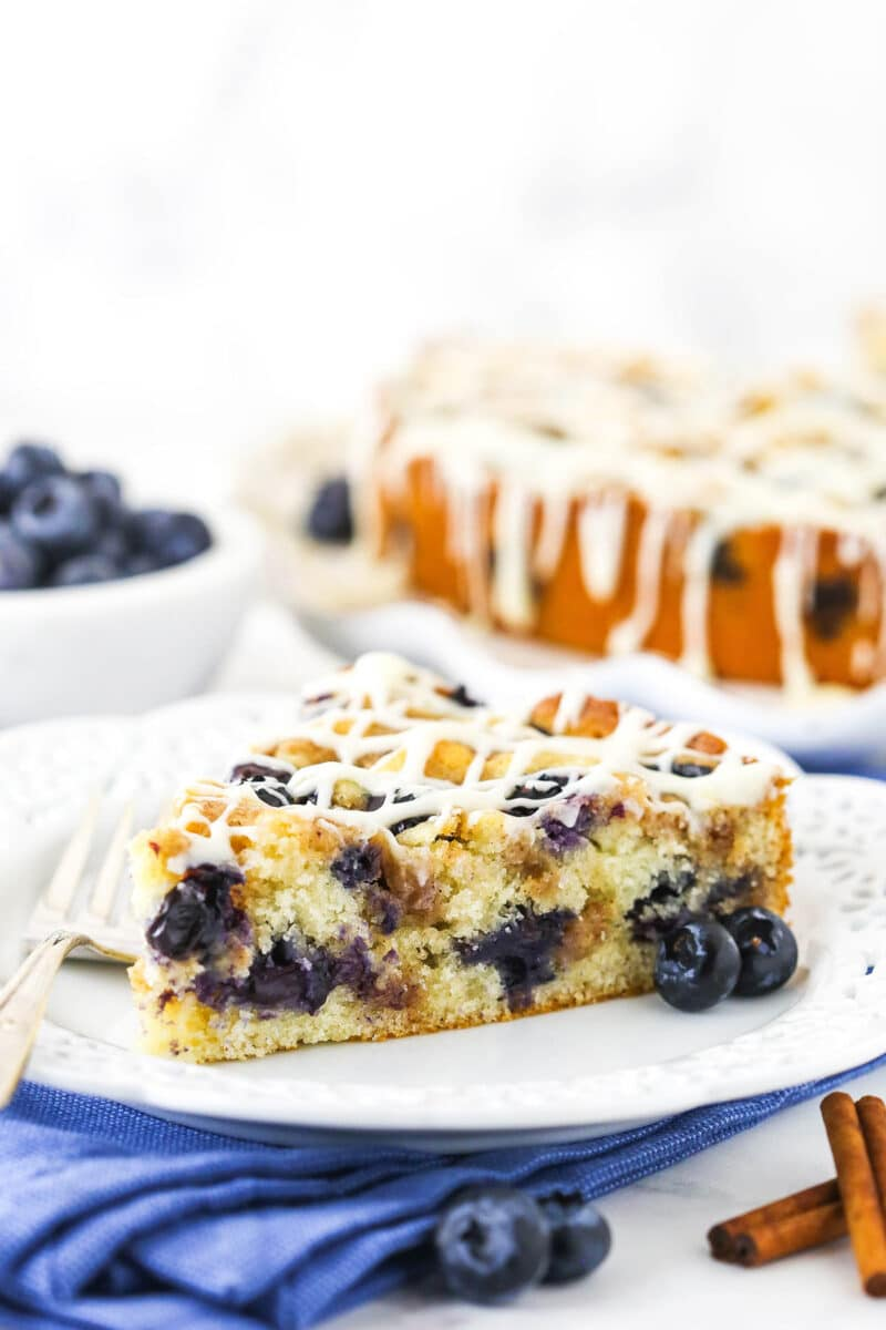 slice of blueberry streusel coffee cake on white plate and blue napkin