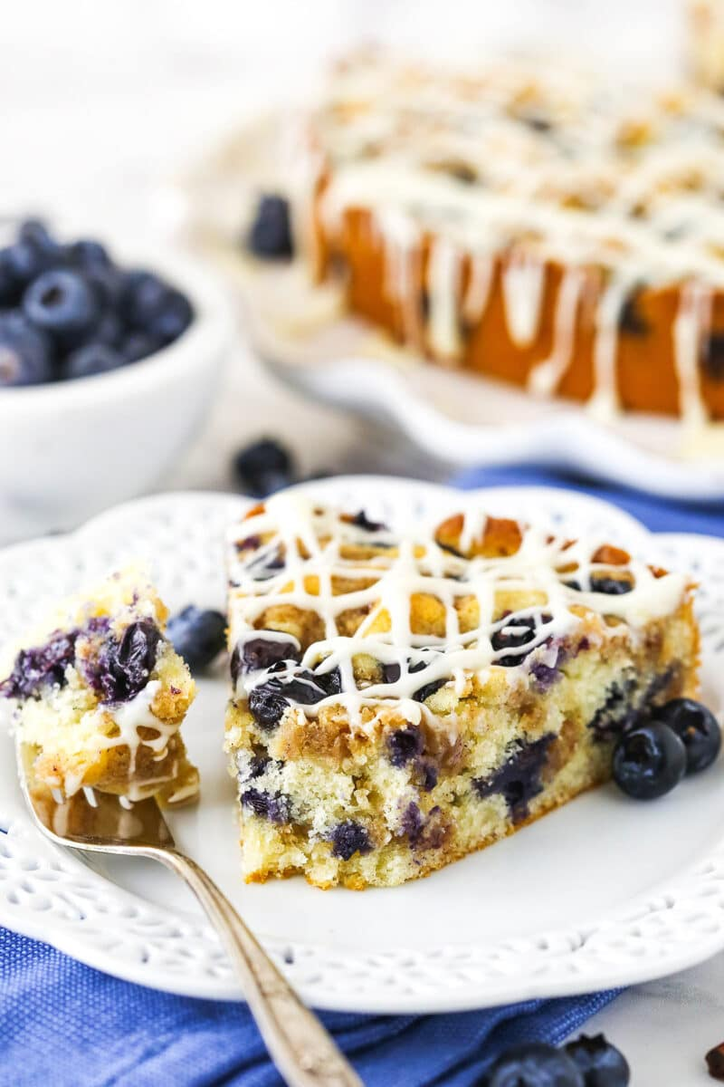 close up of slice of Blueberry Streusel Coffee Cake on white plate with a bite on a fork