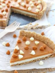 A big slice of White Chocolate Butterscotch Tart on white paper and a fork
