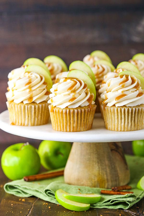 caramel apple cupcakes on a marble and wood cake stand