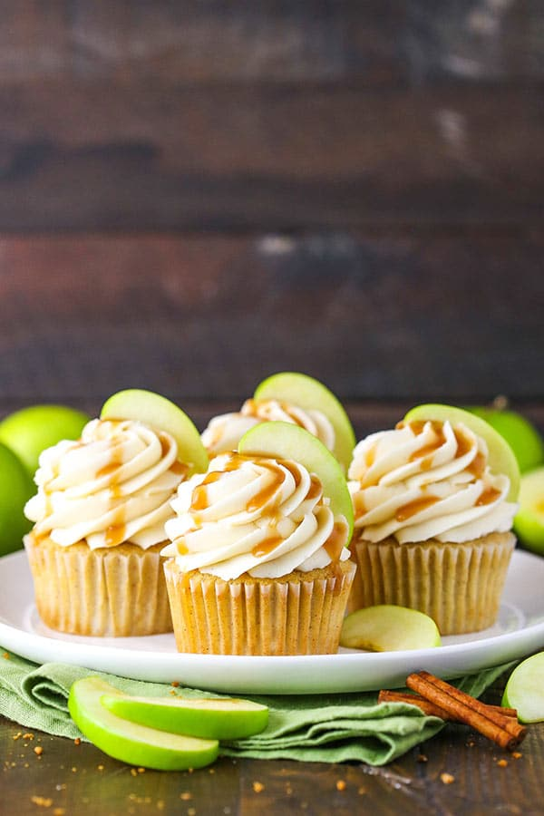 four cupcakes on a white plate with green napkin