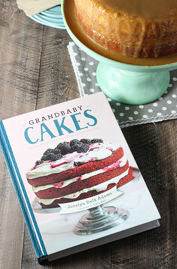 "The book ""Grandbaby Cakes"" next to a cake on a stand."