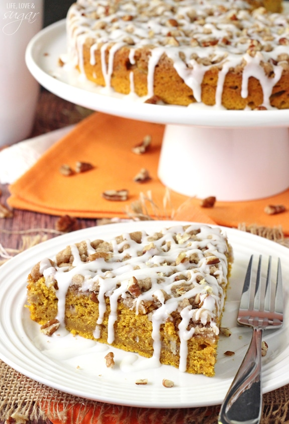 slice Cinnamon Streusel Pumpkin Coffee Cake on white plate with cake stand in background