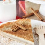 Milk Tart slice on white plate with cinnamon sticks close up