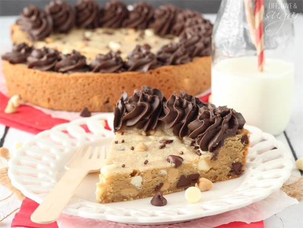 Triple Chocolate Chip Cookie Cake slice on a white plate in front of the whole cake