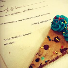 A slice of cookie cake and my authors contract for my new cookbook!