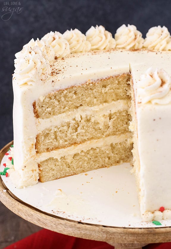Decorated eggnog layer cake with a slice taken out.