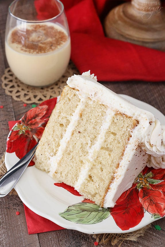Slice of layer cake on a plate next to a glass of eggnog.