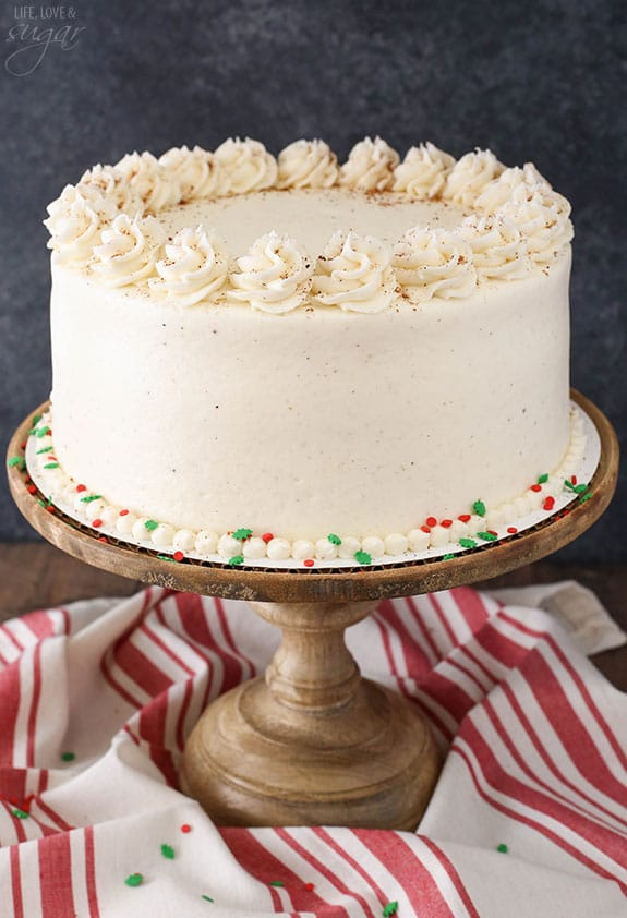 Frosted eggnog cake on a wooden stand.