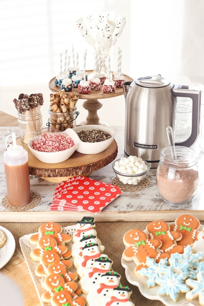 hot chocolate bar with cutout cookies, marshmallows, peppermint pieces, chocolate covered spoons