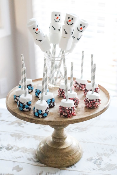 snowman marshmallows and dipped marshmallows on wooden cake stand