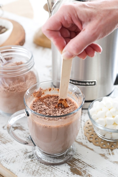 stirring hot chocolate in a mug with wooden spoon