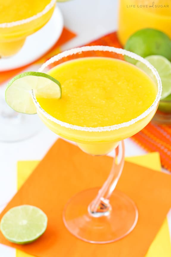 Frozen Mango Margaritas garnished with a lime slice