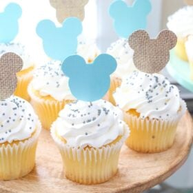 Mickey Mouse Themed Cupcakes with White Frosting and Sprinkles on a Cake Stand
