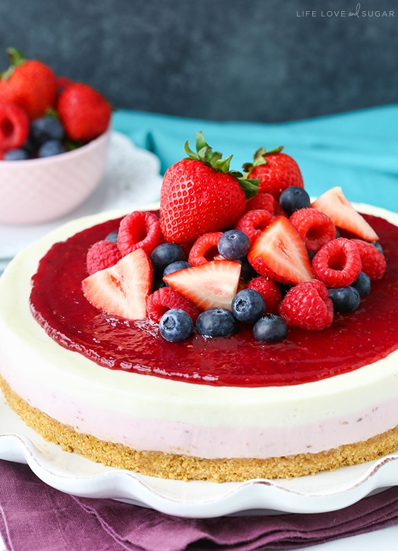 A whole Cheesecake with a layer of berry and vanilla cheesecake, a thick graham cracker crust and a delicious berry topping